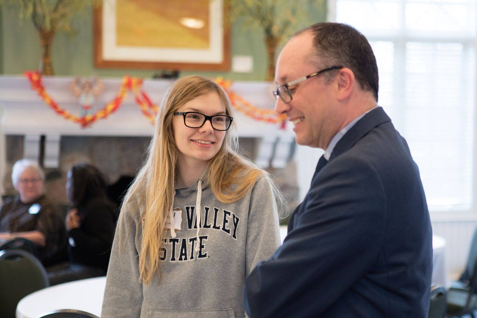 Mike Messner speaking with a female Grand Valley State University student